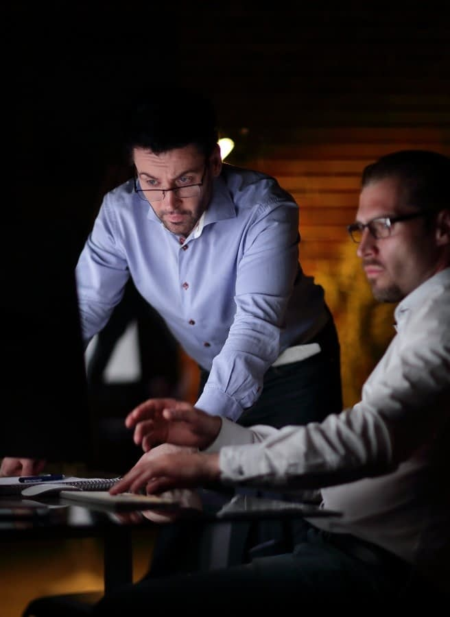 two members of BPS security's investigation services team reviewing clues at a computer