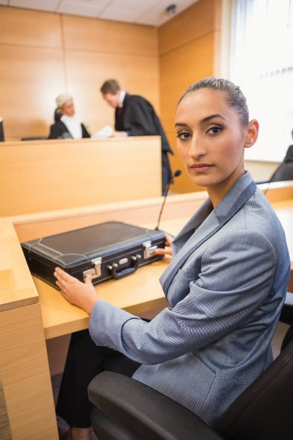 a lawyer in a courtroom looking back at the camera. Her briefcase contains the evidence gathered as a part of BPS Security's surveillance services