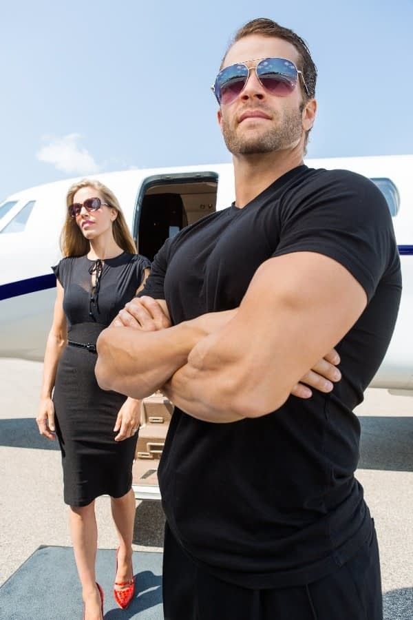 A member of BPS Security's protection services team looking for danger as a woman exits a plane