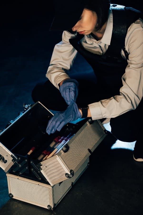 A PI putting her gloves on next to her kit to prepare for a criminal investigation